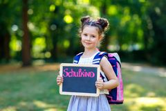 Happy little kid girl standing with desk and backpack or satchel. Schoolkid on first day of elementary class. Healthy royalty free stock photos