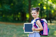 Happy little kid girl standing with desk and backpack or satchel. Schoolkid on first day of elementary class. Healthy stock images