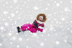 Happy little kid or girl in winter clothes on snow Royalty Free Stock Photos