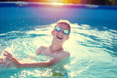 Happy little kid in goggles enjoying summer in swimming pool Royalty Free Stock Photography