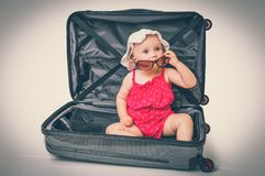 Happy little kid inside suitcase - retro style Stock Photography