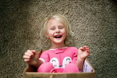 Happy Little Kid Laughing as she Plays in Cardboard Box at her Home stock photography