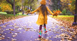 Happy little kid, laughing and playing with falling autumn leaves in park