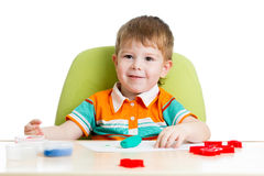 Happy little kid playing with colorful clay Stock Photography