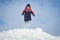 Happy little kid is playing in snow Stock Photos