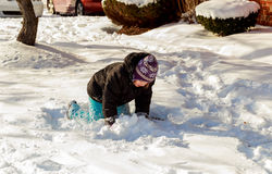 Happy little kid is playing in snow, good winter weather. Little girl playing in the street with snow Royalty Free Stock Image