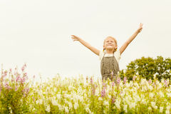 Happy little kid with raised up arms in green  field of flowers. Royalty Free Stock Images