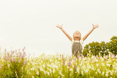 Happy little kid with raised up arms in green  field of flowers. Royalty Free Stock Image