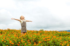 Happy little kid with raised up arms in green  field of flowers. Stock Image