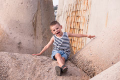 Happy little kid sitting on concrete breakwater. Happy little boy in sailor stripes singlet and jean shorts sitting on concrete breakwater stock photography