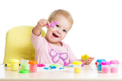 Happy little kid sitting at table and playing Royalty Free Stock Photos