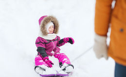 Happy little kid on sled outdoors in winter Stock Photo