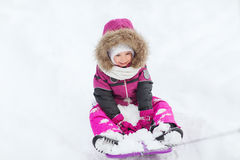Happy little kid on sled outdoors in winter Royalty Free Stock Photography