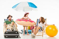Happy little kid standing with flotation ring between parents sitting on sun loungers. Isolated on white, travel concept royalty free stock image