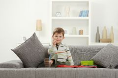 Happy little kid with toys sitting on sofa Royalty Free Stock Photos
