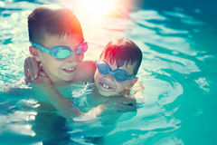 Happy little kids have fun in swimming pool graded Stock Image