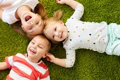 Happy little kids lying on floor or carpet Stock Image