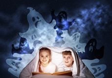 Happy little kids reading book in bed. Happy little kids reading magic fairy tales in bed. Brother and sister together hiding under blanket. Little friends in royalty free stock photo