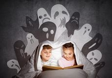 Happy little kids reading book in bed. Happy little kids reading magic fairy tales in bed. Brother and sister together hiding under blanket. Little friends in stock images