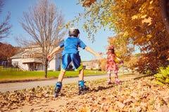 Happy little kids roller skating in autumn park stock image