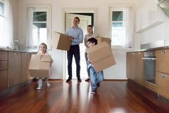 Happy little kids run with boxes into new bought house royalty free stock photography