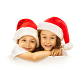 Happy little kids in Santa hat peeking from behind Stock Images