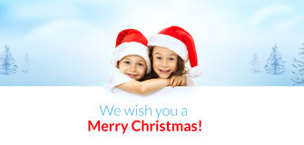 Happy little kids in Santa hat peeking from behind. Blank sign billboard. Isolated on white background. Space for Your Text. Sale, holidays, christmas, new year stock image
