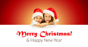 Happy little kids in Santa hat peeking from behind royalty free stock photography