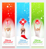 Happy little kids in Santa hat peeking from behind Stock Photography