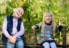 Happy Little Kids Sitting on a Wooden Garden Fence Stock Photos