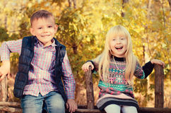 Happy Little Kids Sitting on a Wooden Garden Fence Royalty Free Stock Photo