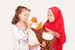 Happy little Muslim girls playing with sheep toy - celebrating E Stock Photo