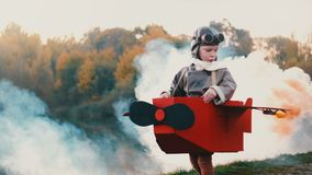 Happy little pilot boy running along sunset lake in fun cardboard plane costume dreaming of aviation career slow motion. Excited Caucasian male child stock footage