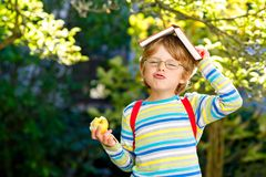 Happy little preschool kid boy with glasses, books, apple and backpack on his first day to school or nursery. Funny royalty free stock photos