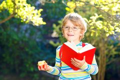 Happy little preschool kid boy with glasses, books, apple and backpack on his first day to school or nursery. Funny. Healthy child outdoors on warm sunny day royalty free stock photography