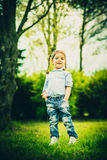 Happy little pretty girl outdoor in the park Royalty Free Stock Photos