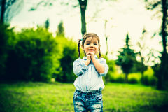Happy little pretty girl outdoor in the park Stock Photos