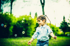 Happy little pretty girl outdoor in the park Stock Images
