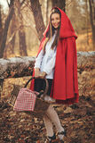 Happy little red riding hood poses in the forest. Happy and smiling little red riding hood posing in the forest Royalty Free Stock Images