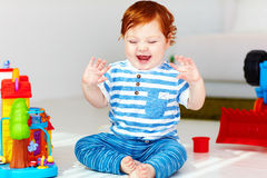 Happy little redhead baby playing with toy house royalty free stock photo