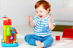 Happy little redhead baby playing with toy house royalty free stock image