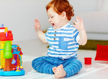 Happy little redhead baby playing with toy house stock images
