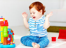 Happy little redhead baby playing with toy house royalty free stock photos