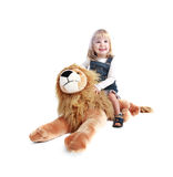 Happy little rider. Happy little girl riding her toy lion (over white background with shadow Royalty Free Stock Photography