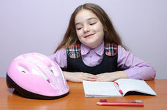 Happy little school girl doing homeworks at desk. Portrait of a little school girl doing homeworks at desk smile while looking at a bike helmet Royalty Free Stock Images