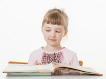 Happy little school girl learning to read. White background Royalty Free Stock Photos