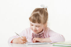 Happy little school girl learning to write. White background Royalty Free Stock Photography
