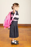Happy Little School Girl Wearing Uniform and Carrying her Packpack - Pointing to You stock image
