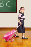 Happy Little School Girl Wearing Uniform and pulling her bag at stock photo