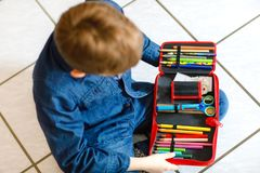 Happy little school kid boy searching for a pen in pencil case. Healthy schoolchild with glasses grab thinks for lessons stock images